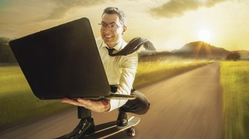 Business-Mann auf Skateboard mit Laptop in der Hand