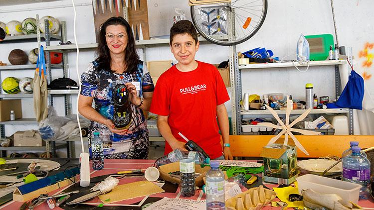 """Maria Smodics-Neumann mit Kind beim Besuch der """"Unmöglichen Werkstatt"""" in der Spielstadt Otopia."""